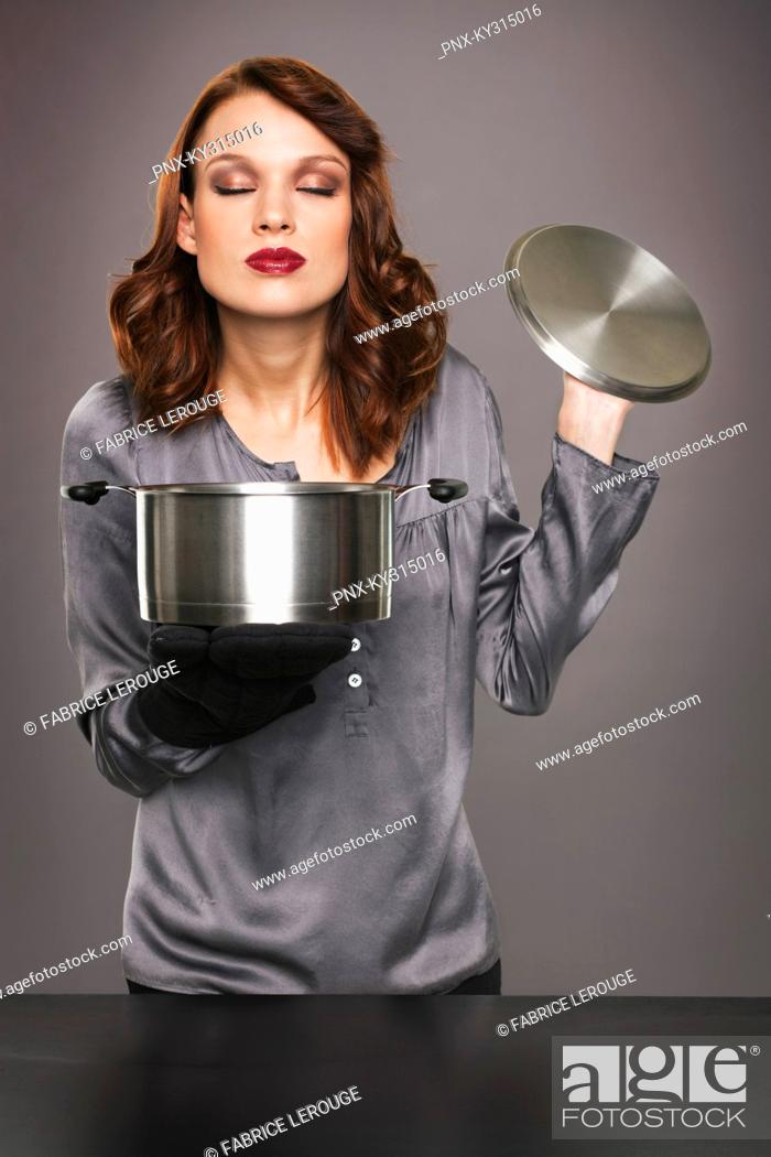 Stock Photo: Young woman smelling aroma from stew pot.