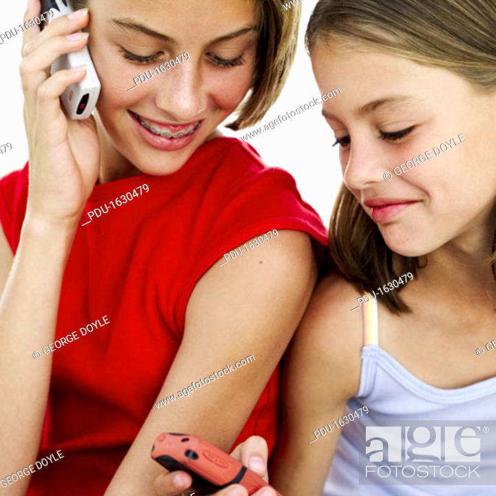 Stock Photo: two girls (8-12) using mobile phones.
