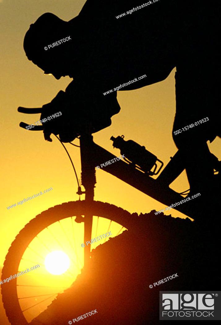 Stock Photo: Silhouette of person mountain biking.
