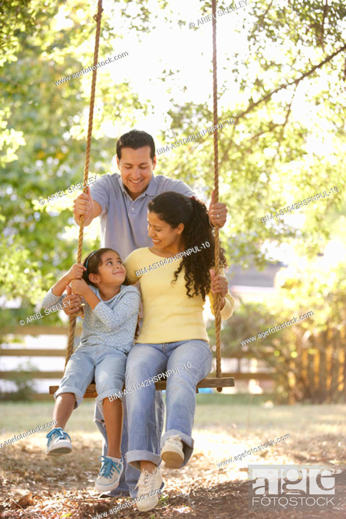 Stock Photo: Man pushing daughter and wife on swing.