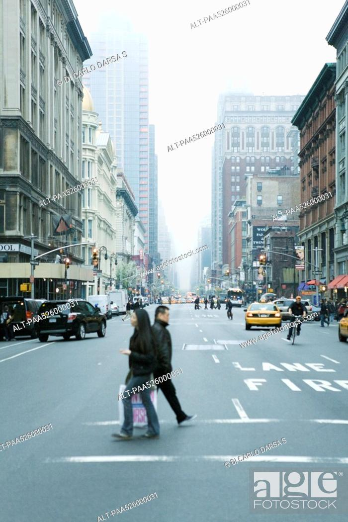 Stock Photo: Pedestrians crossing street in crosswalk at W 19th Street and 6th Avenue Chelsea, New York, facing NE.