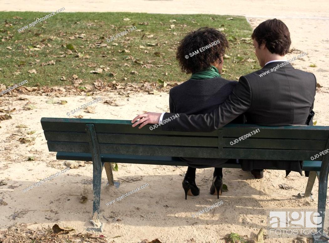 Stock Photo: Couple sitting outdoors on bench.