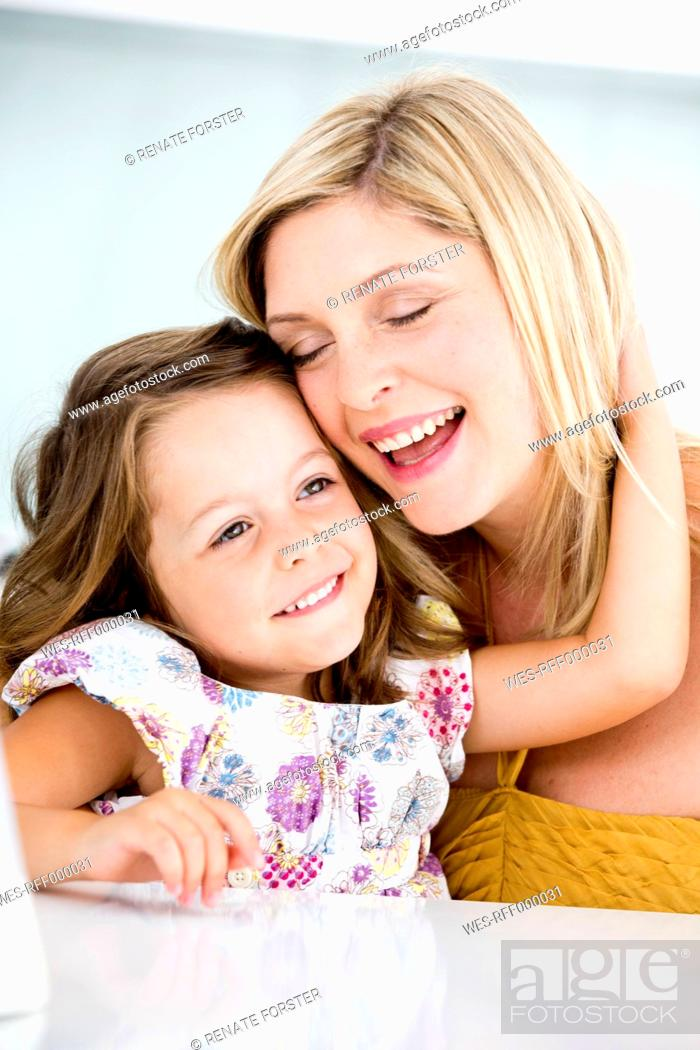 Stock Photo: Germany, Mother and daughter smiling, close-up.
