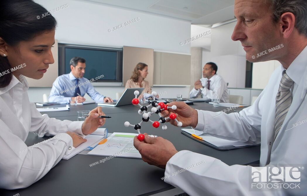 Stock Photo: Scientist and businesswoman examining molecular model in conference room.