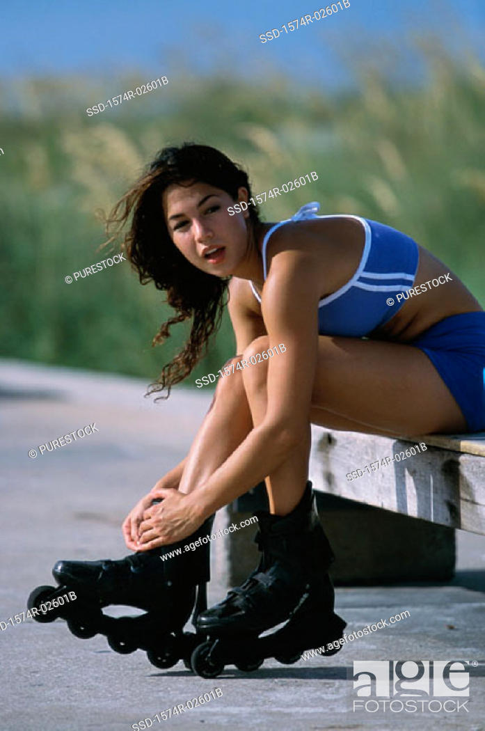 Stock Photo: Portrait of a young woman adjusting her inline skates.