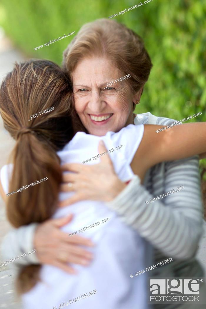 Stock Photo: A senior woman hugging a young woman.
