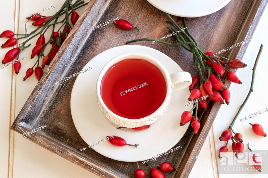 Stock Photo: Rose hip tea in a white vintage cup.