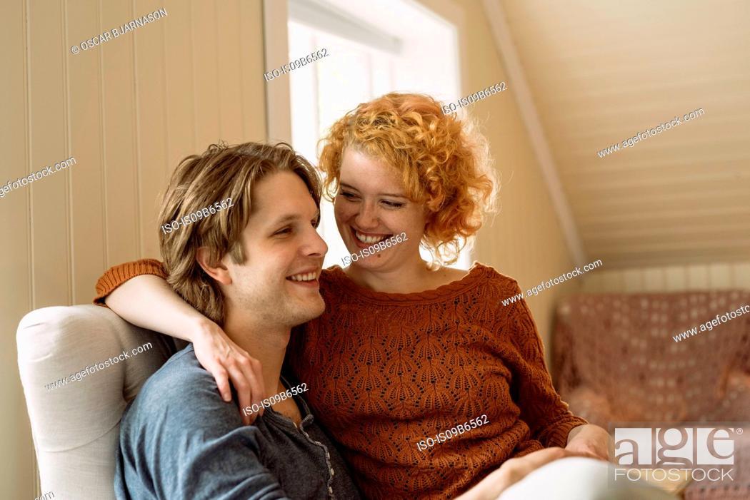 Stock Photo: Woman sitting on man's lap smiling.