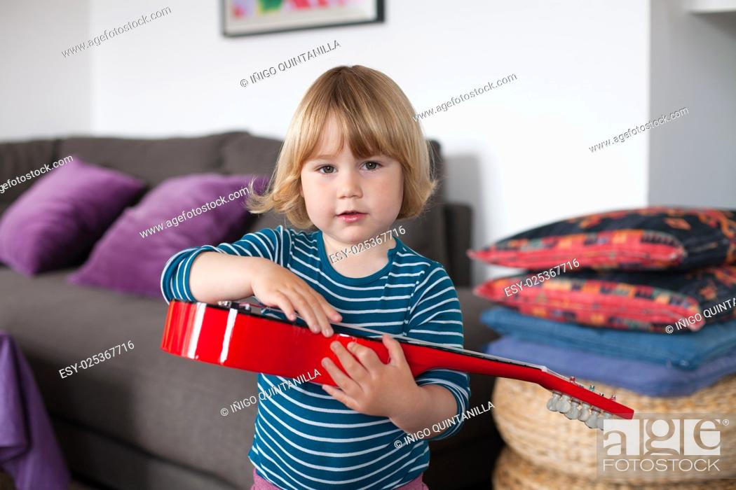 Stock Photo: blonde two years old child with striped blue and white sweater inside home playing with hand red spanish little guitar and looking.