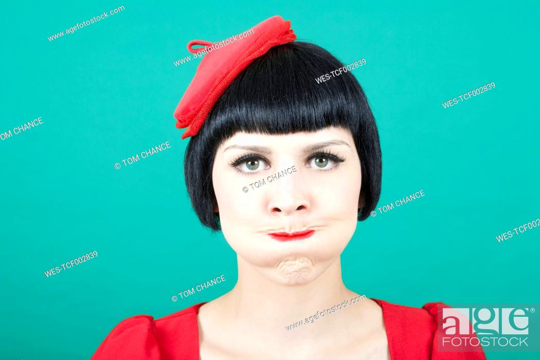 Stock Photo: Close up of young woman against green background.
