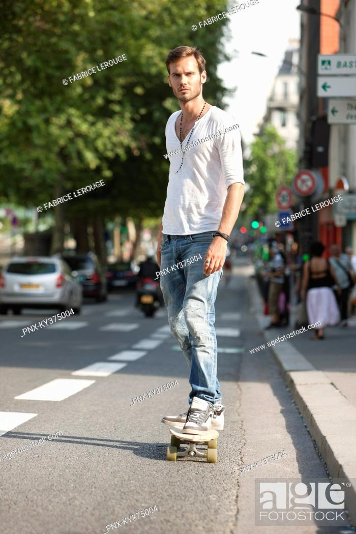 Stock Photo: Man skateboarding on the road, Paris, Ile-de-France, France.