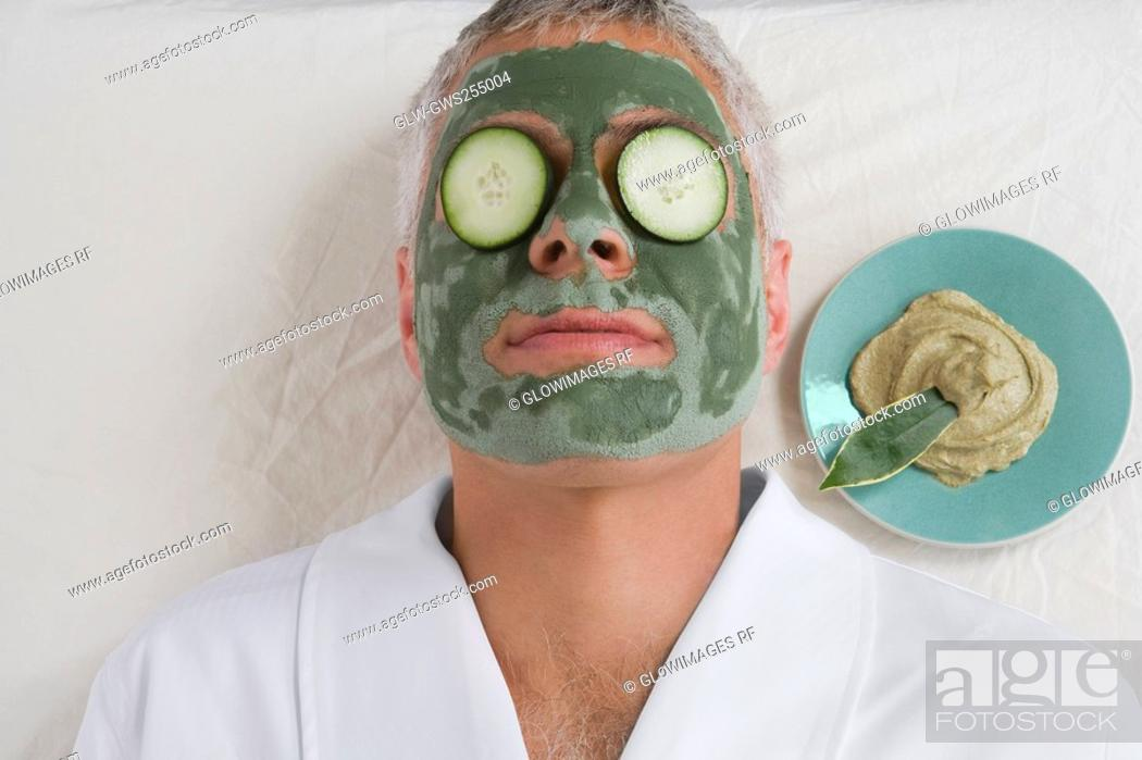 Stock Photo: Close-up of a mature man lying down with a face pack and cucumber slices on her eyes.