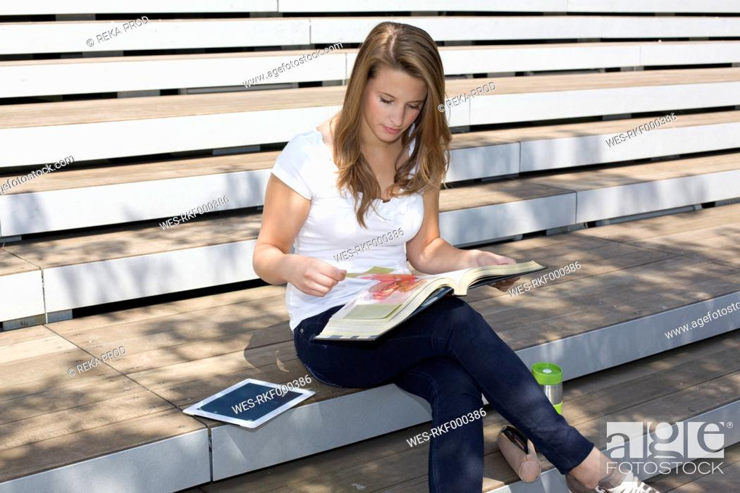 Stock Photo: Europe, Germany, North Rhine Westphalia, Duesseldorf, Young student sitting on staircase and learning book.