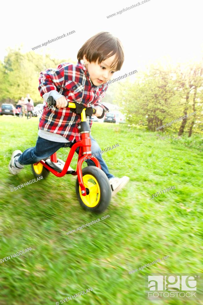 Stock Photo: A young boy running on a balance bicycle.