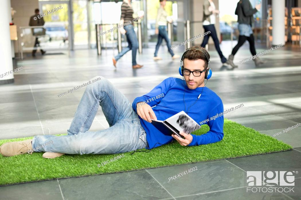 Stock Photo: Businessman listening to music and reading book while relaxing on grass mat in an office lobby.