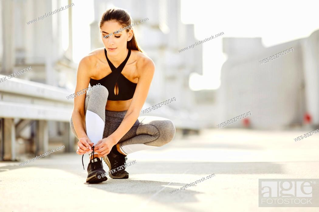 Stock Photo: Young woman tying her shoes before workout.
