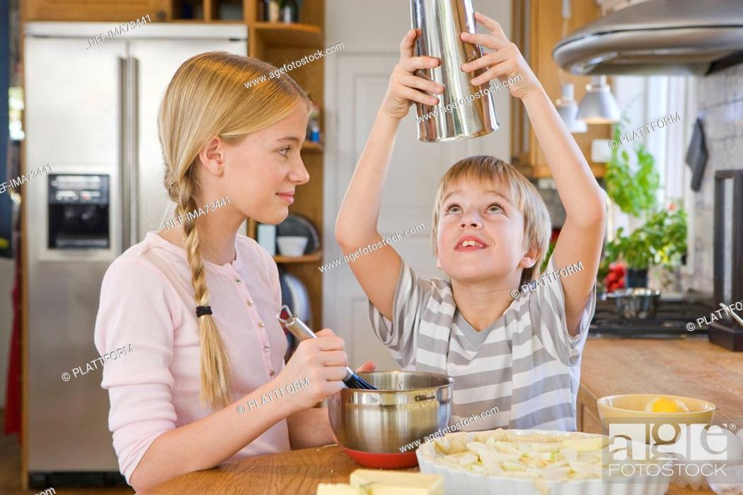 Stock Photo: Sister and brother making a cake, Sweden.