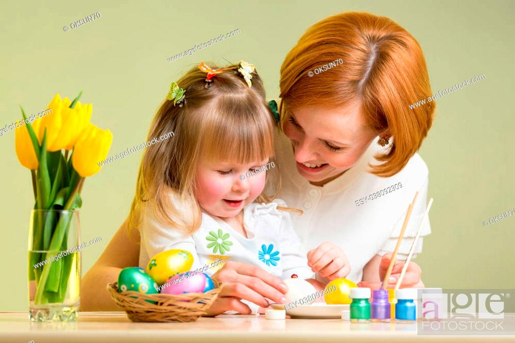 Stock Photo: mother and kid girl painting easter eggs together.