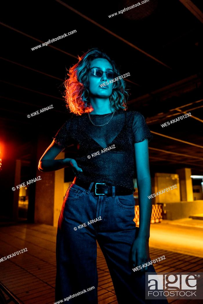 Stock Photo: Stylish young woman at night in the city, wearing sunglasses.