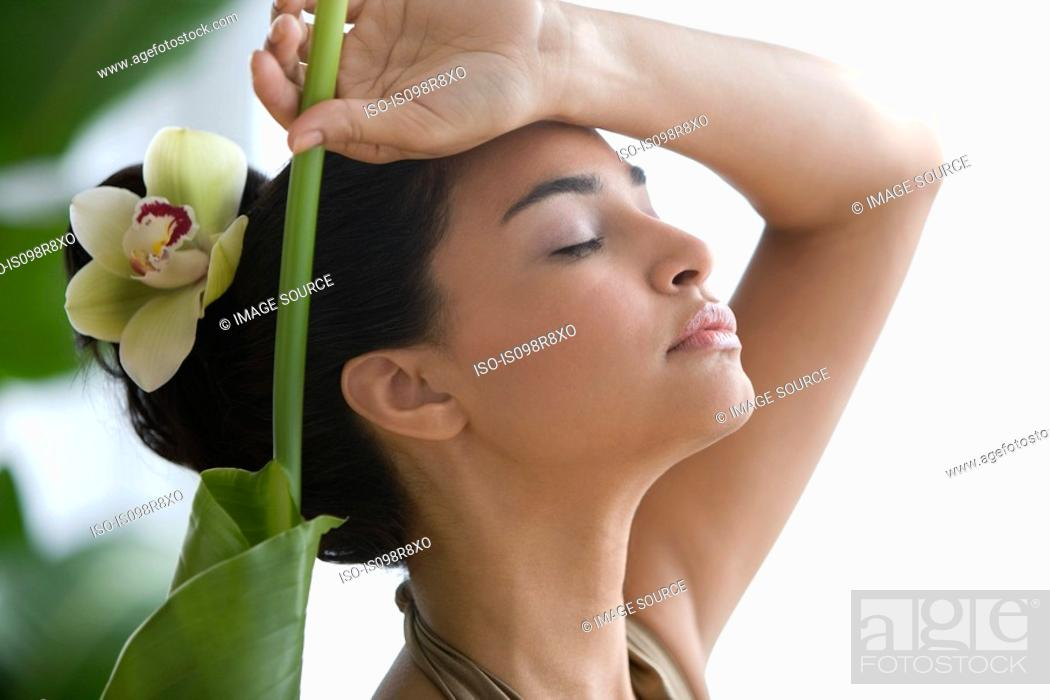 Stock Photo: Young woman with leaf and flower in hair.