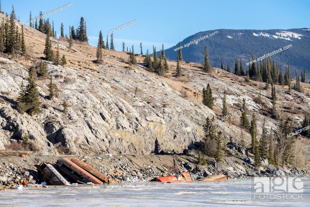 Stock Photo: Crew assessing a freight train derailment in the frozen Athabasca River in Jasper National Park, Alberta, Canada.