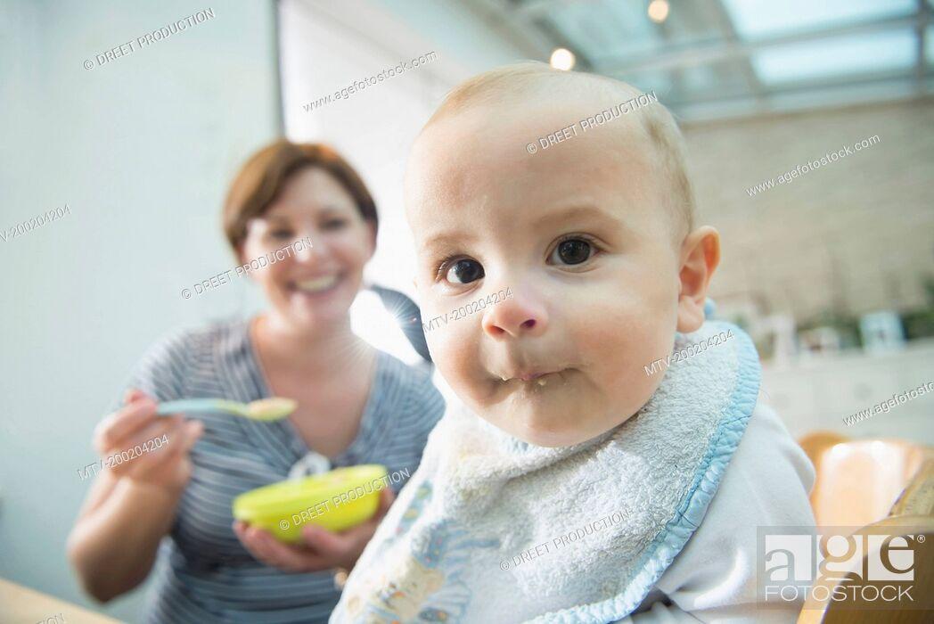 Stock Photo: Mother feeding little son.