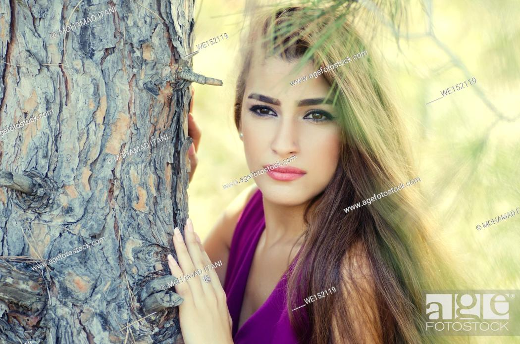 Stock Photo: Beautiful young woman leaning against a tree looking away.