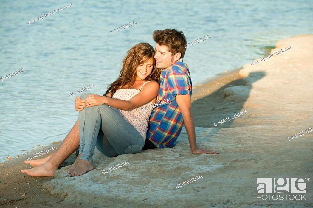 Stock Photo: Young couple sitting near lake.