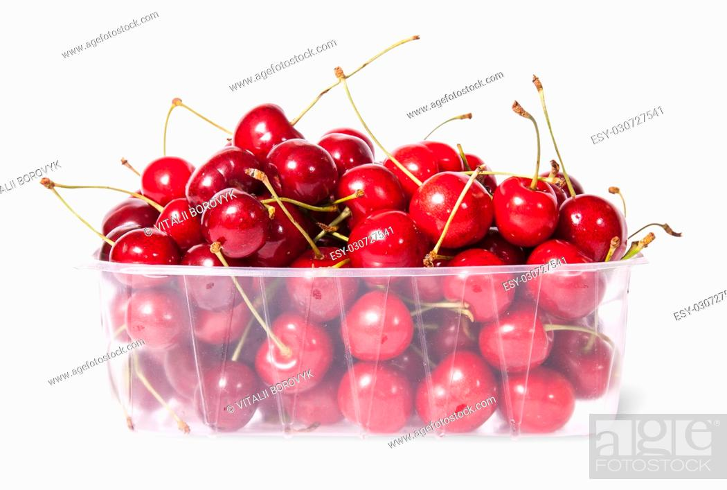 Stock Photo: Red juicy sweet cherries in a plastic tray isolated on white background.