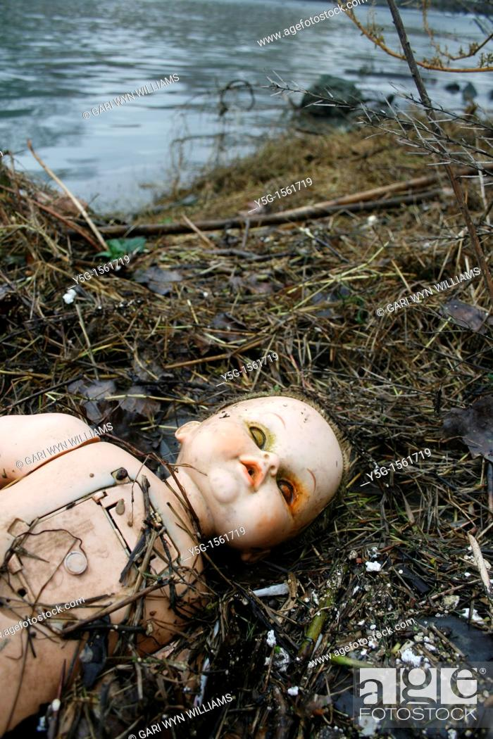 Stock Photo: baby doll washed up on river bank.