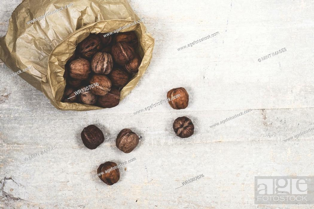Stock Photo: High angle close up of brown paper bag with fresh walnuts.