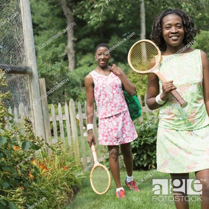 Stock Photo: Two mid adult women holding tennis rackets and walking in a lawn.