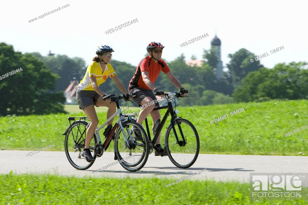 Stock Photo: Germany, Bavaria, Man and woman riding bicycle.
