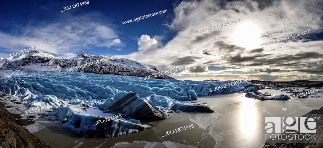 Stock Photo: Blue ice of the Svinafellsjokull glacier flowing from the mountains to a small lagoon.