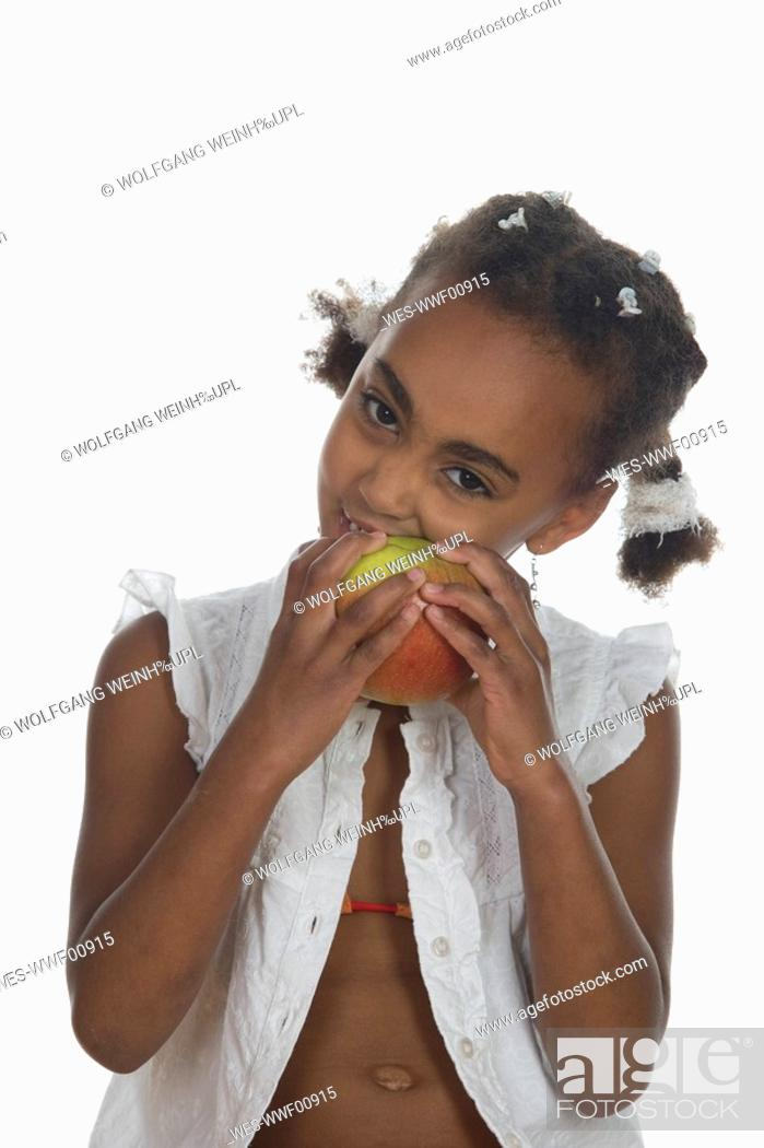 Stock Photo: African girl 6-7 biting into apple, portrait.