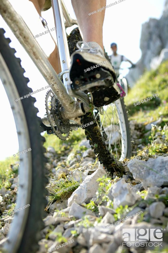 Stock Photo: Two people on mountainbikes going downhill part of, selective focus.