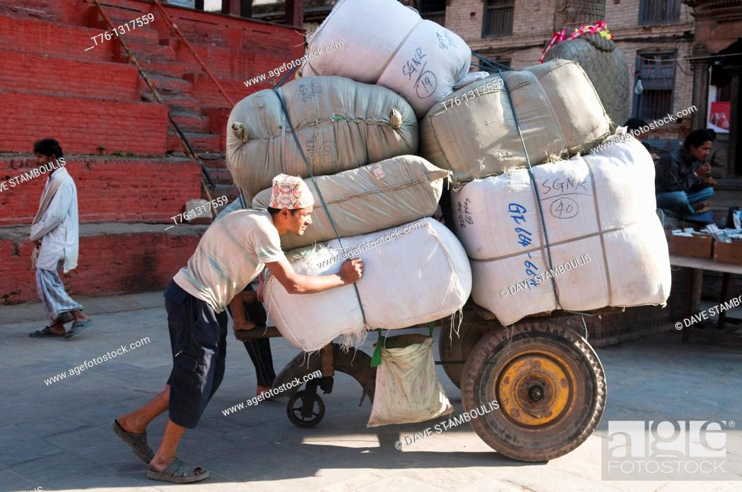 Stock Photo: a porter and his load in Durbar Square in Kathmandu, Nepal.