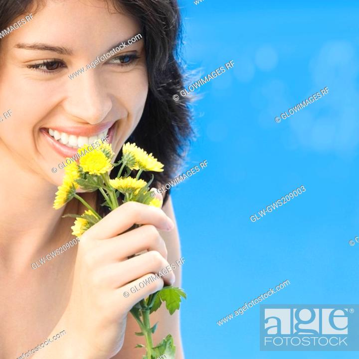 Stock Photo: Close-up of a young woman holding flowers and smiling.