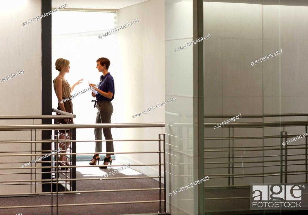 Stock Photo: Businesswomen talking in window of modern office.