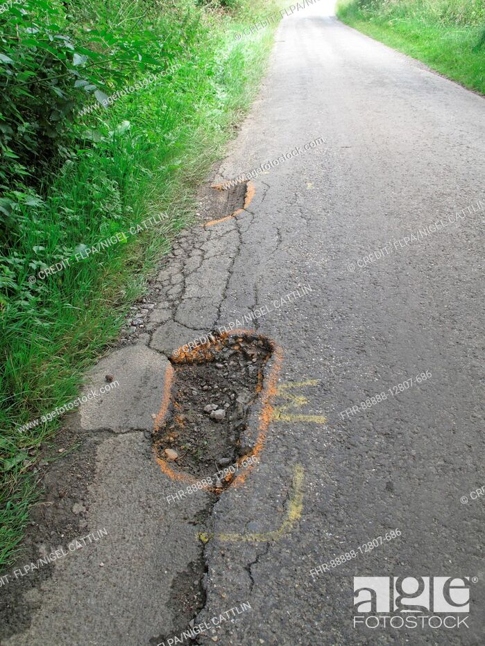 Imagen: Potholes in broken tarmac country road marked to warn cyclists of danger, Berkshire, England, July.