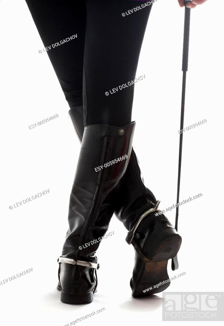 Stock Photo: beautiful legs in black leather horseman boots with riding-crop over white.