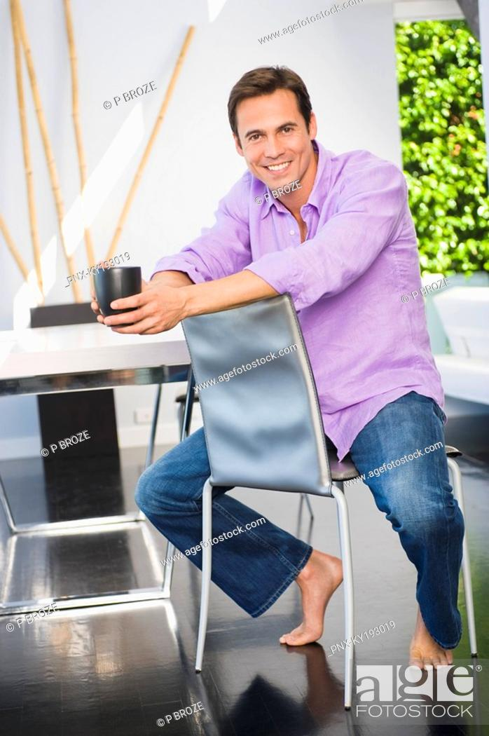 Stock Photo: Portrait of a man holding a coffee cup and smiling.