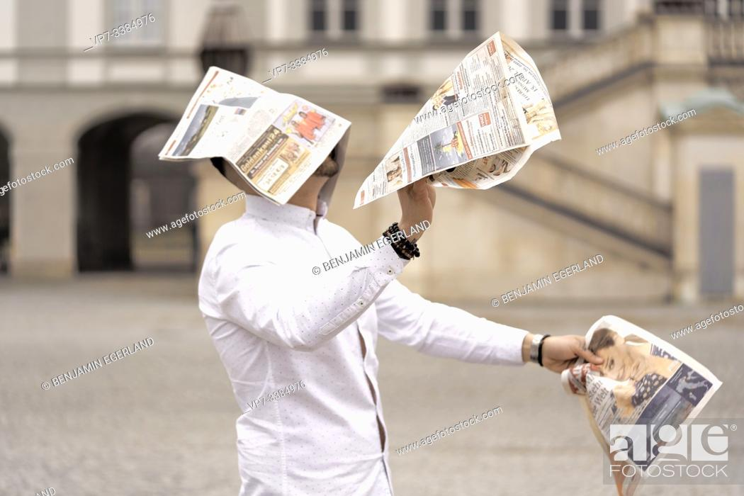 Imagen: Man assailed by flying newspapers, in Munich, Germany.
