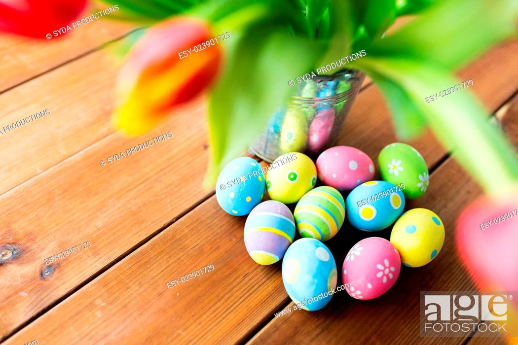 Imagen: easter, holidays, tradition and object concept - close up of colored easter eggs and tulip flowers in bucket on wooden table.