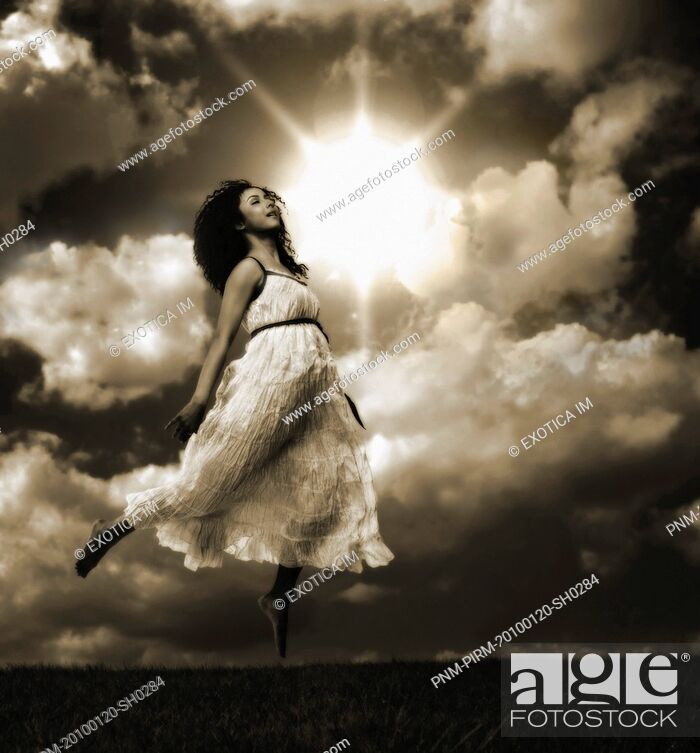 Stock Photo: Woman jumping in a field.