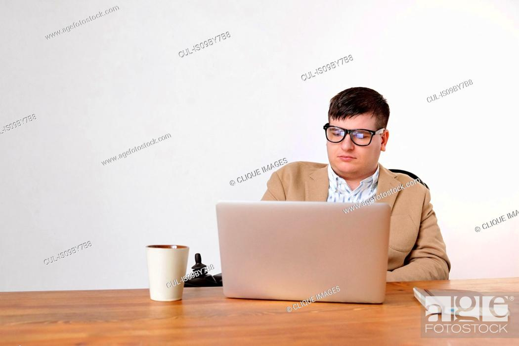 Stock Photo: Man working on laptop in home office.