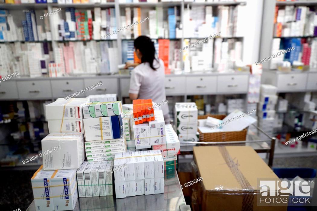 Stock Photo: Hospital pharmacy. Pharmacist checking inventory. Tam Duc Cardiology Hospital. Ho Chi Minh City. Vietnam.