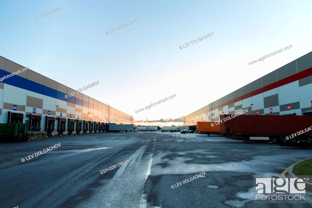 Stock Photo: logistic, storage, shipment, transportation and loading concept - warehouse gates and trucks loading.