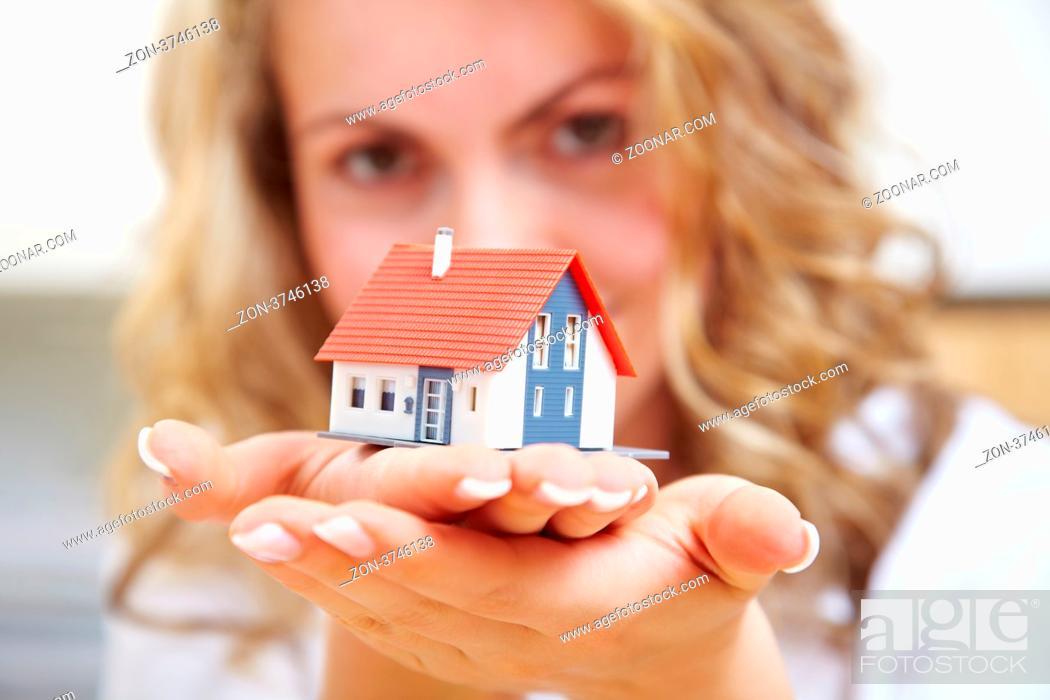 Imagen: Frau trägt ein kleines Einfamilienhaus auf ihren Händen.