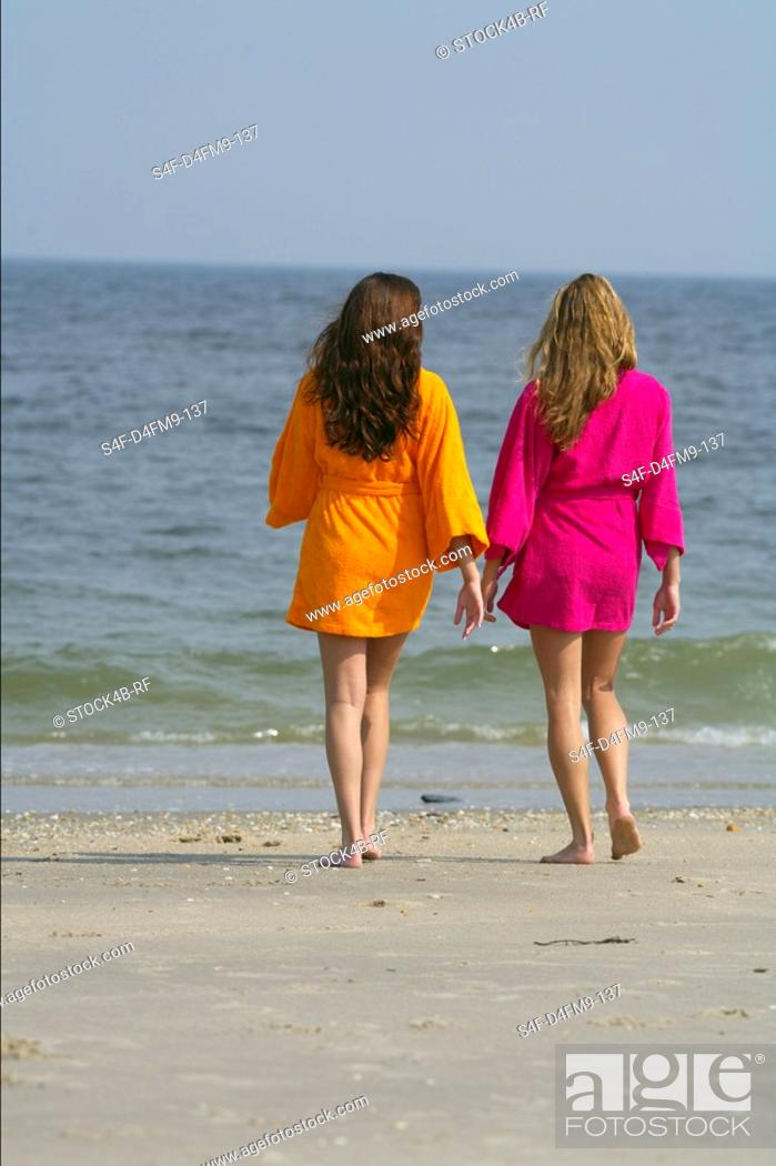Stock Photo: Two young women promenading at the beach in bathrobes.